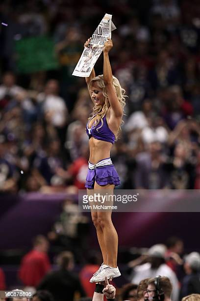 A cheerleader for the Baltimore Ravens holds up a newspaper declaring the Ravens Champs afer they won 3431 against the San Francisco 49ers during...