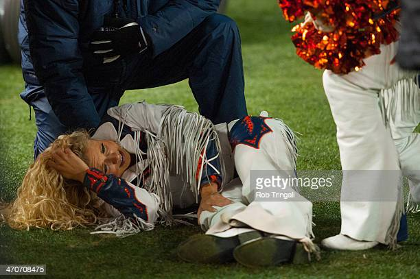 A cheerleader for the Denver Broncos lies on the field after getting knocked over during the game between the Denver Broncos and the Kansas City...