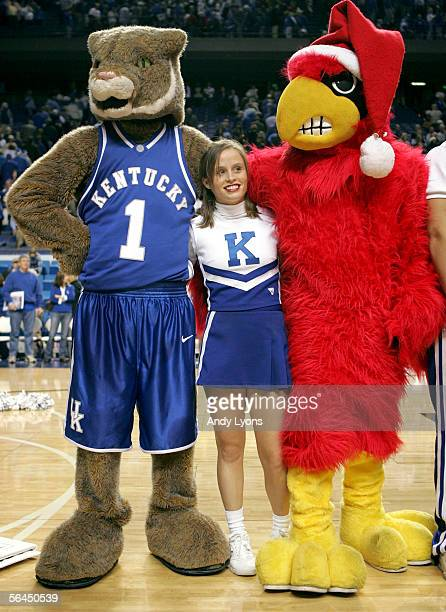 """Cheerleader for the Kentucky Wildcats stands between the mascots for Kentucky and the Louisville Cardinals as they sing """"My old Kentucky Home"""" after..."""