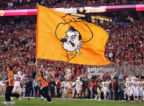 A cheerleader for the Oklahoma State Cowboys runs on the field with a giant flag in support of his school against the Stanford Cardinal during the...