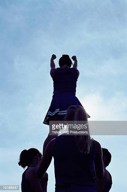 Cheerleader forming pyramid