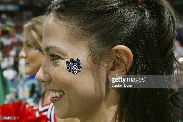 A cheerleader from the University of Arizona smiles as she displays a temporary tatoo of a Wildcat paw print with the big A inside it on her face...