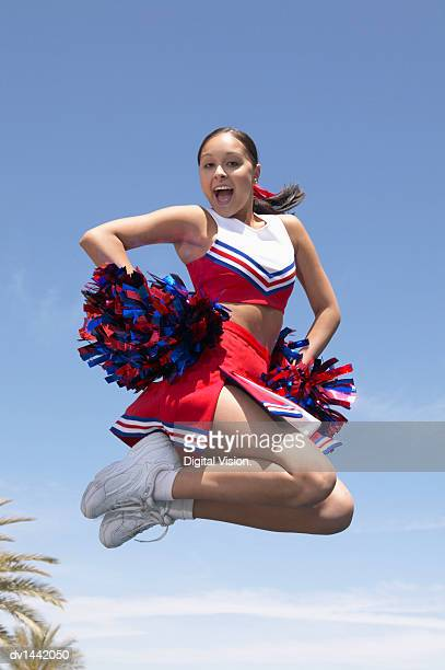 cheerleader holding pompoms, jumping and cheering - チアリーダー ストックフォトと画像