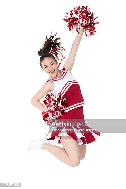 cheerleader in action with her pom-poms - asian cheerleaders stock photos and pictures