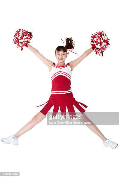 cheerleader in action with her pom-poms - チアリーダー ストックフォトと画像