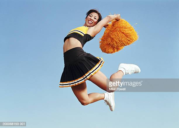 cheerleader jumping in mid air, holding pompoms , portrait - asian cheerleaders stock photos and pictures