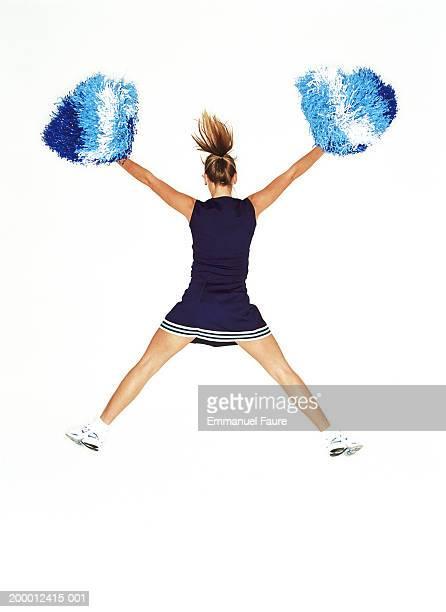 Cheerleader jumping in mid air, rear view
