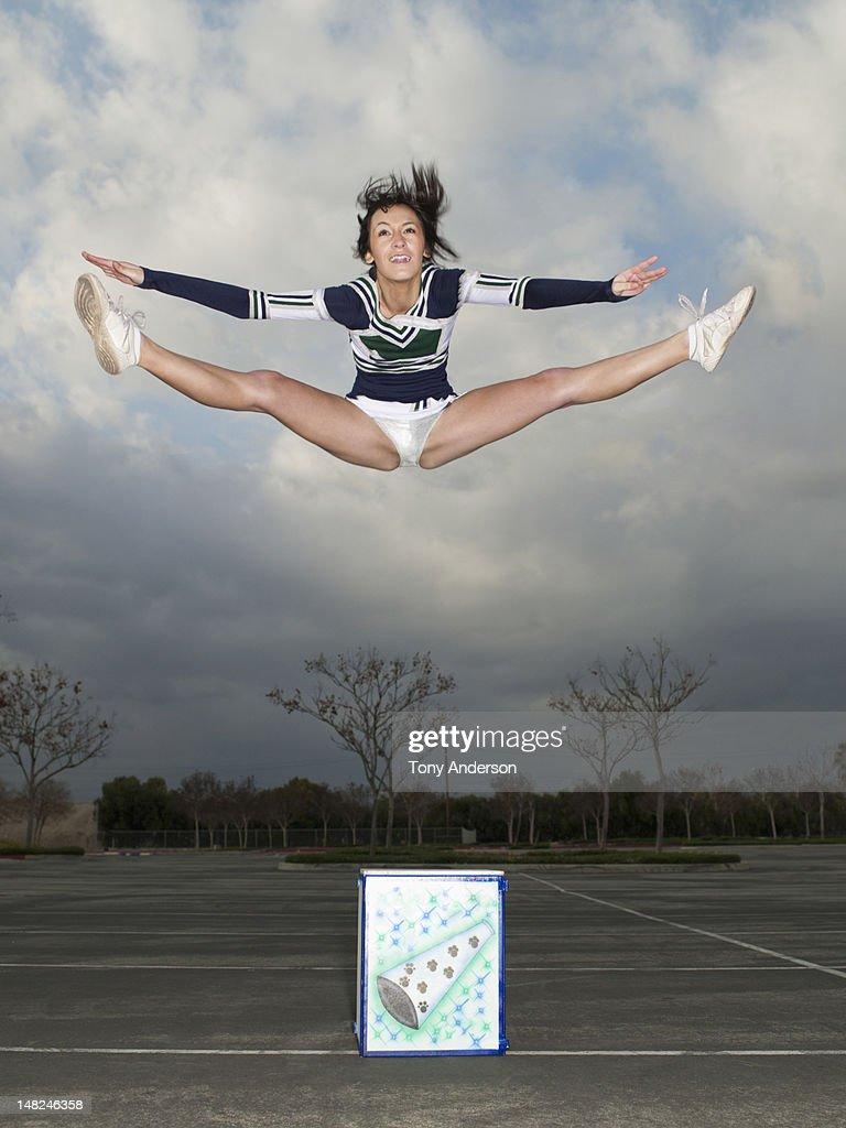 Cheerleader jumping off box : Stock Photo