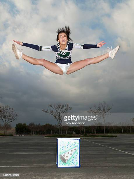cheerleader jumping off box - cheerleaders stock photos and pictures