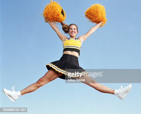 cheerleader jumping with pompoms in mid air stock photo getty images. Black Bedroom Furniture Sets. Home Design Ideas