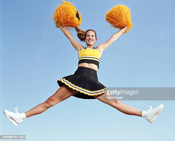 Cheerleader jumping with pompoms in mid air