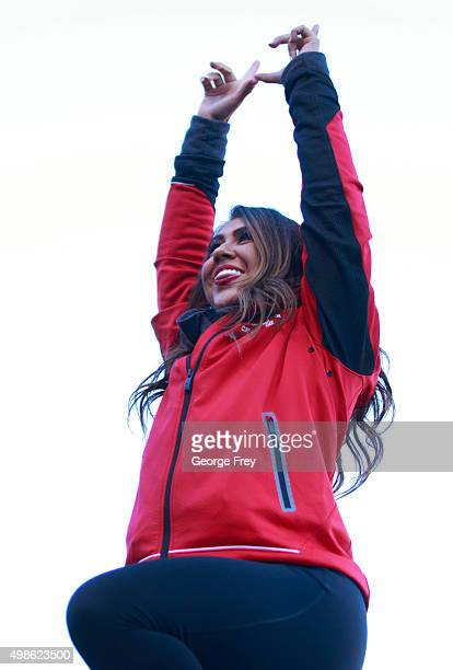 A cheerleader of the Utah Utes makes a U with her fingers at a game against the UCLA Bruins during the first half of a college football game at Rice...