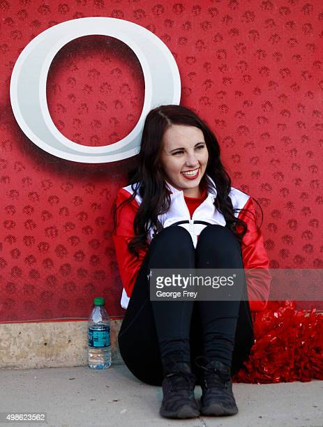 A cheerleader of the Utah Utes sits against a wall to warmup at a game against the UCLA Bruins during the first half of a college football game at...