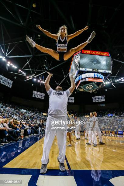 A cheerleader performs highflying splits during a timeout during the game between the Nevada Wolf Pack and the Brigham Young Cougars at Lawlor Events...