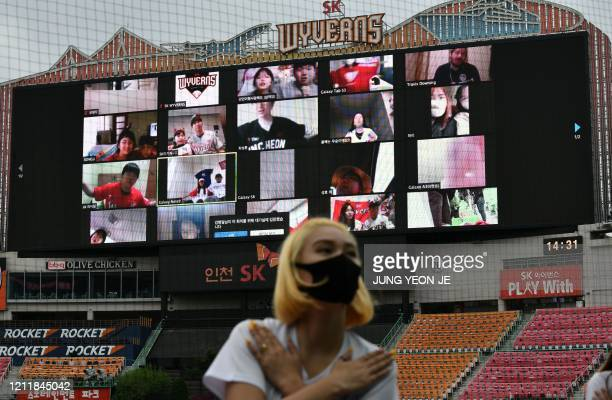 TOPSHOT A cheerleader performs in front of a large screen displaying baseball fans cheering from their homes during the opening game of South Korea's...