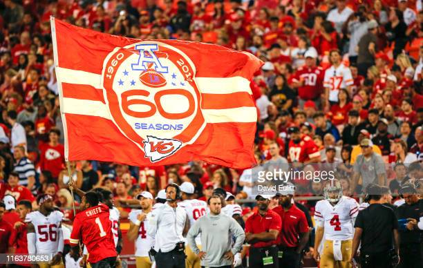 Cheerleader runs with a flag commemorating the 60th season of the Kansas City Chiefs during a preseason game against the San Francisco 49ers at...