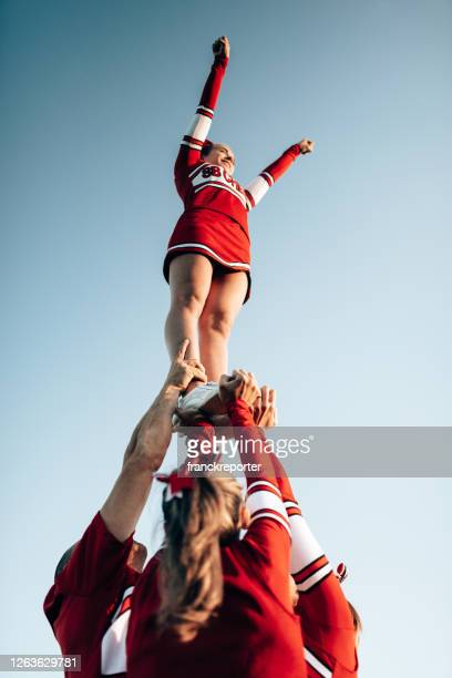 cheerleader team creating a perform - cheerleader stock pictures, royalty-free photos & images