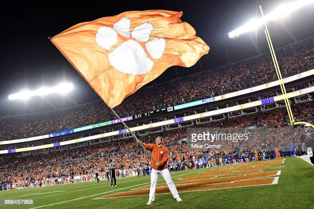 A cheerleader waves a Clemson Tigers flag after the Tigers' score a touchdown against the Miami Hurricanes during the ACC Football Championship at...
