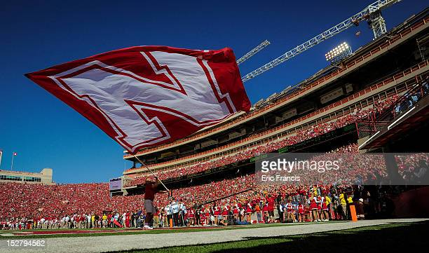 A cheerleader waves a flag after the Nebraska Cornhuskers score against the Idaho State Bengals during their game at Memorial Stadium on September 22...