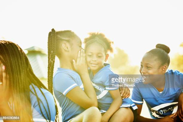 Cheerleader whispering secret to smiling young teammate