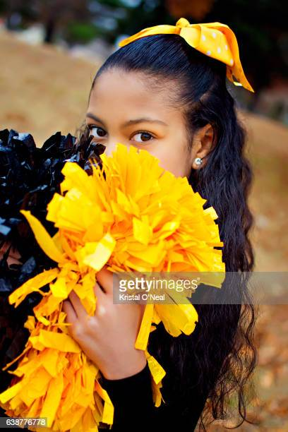 cheerleader with black and gold pom-poms - black cheerleaders stock photos and pictures