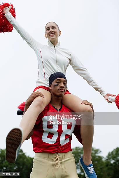 cheerleader with football player - candid cheerleaders stock photos and pictures