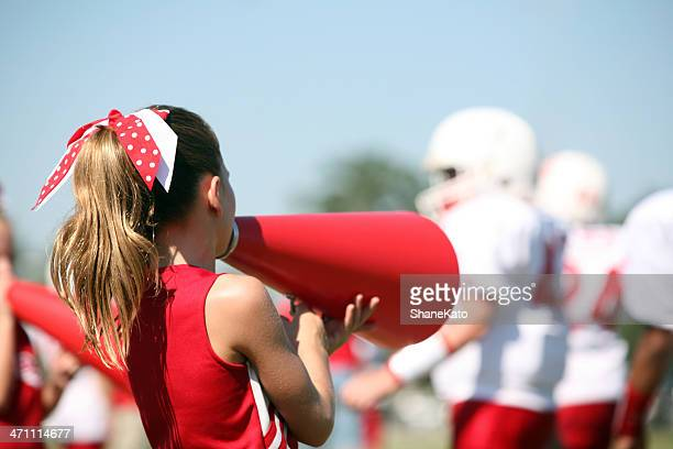 cheerleader with megaphone cheers for her football team - cheerleaders stock photos and pictures
