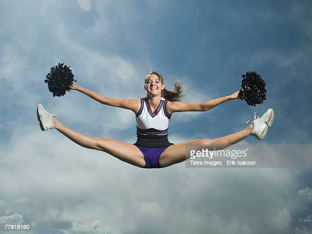 cheerleader with pom poms jumping - cheerleaders stock photos and pictures