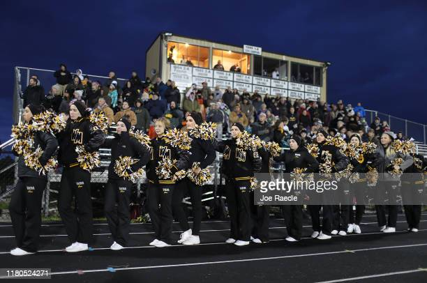 Cheerleaders and fans of the West Marshall high school football team listen to the National Anthem before the start of the home coming game against...