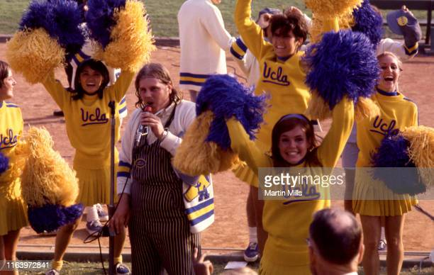 Cheerleaders and Steven Halpern, the mascot of the University of California Los Angeles, try to get the crowd involved in the game during an NCAA...