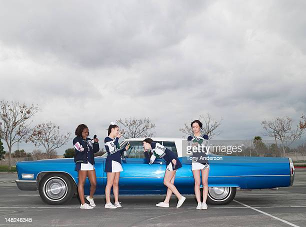 cheerleaders applying make up by car - black cheerleaders stock photos and pictures