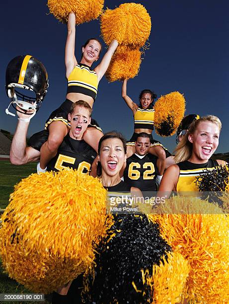 Cheerleaders celebrating with football players on field, portrait