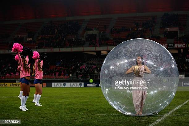 Cheerleaders dance as a woman in a giant plastic ball holding a gold rugby ball poses prior to the Amlin Challenge Cup between Stade Francais and...