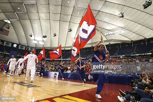 Cheerleaders for the Dayton Flyers runs by players from the Kansas Jayhawks during warm ups for their second round of the NCAA Division I Men's...