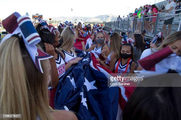 Cheerleaders for the Herriman Mustangs gather a large American Flag for an infield National Anthem ceremony before their game against the Davis Darts...