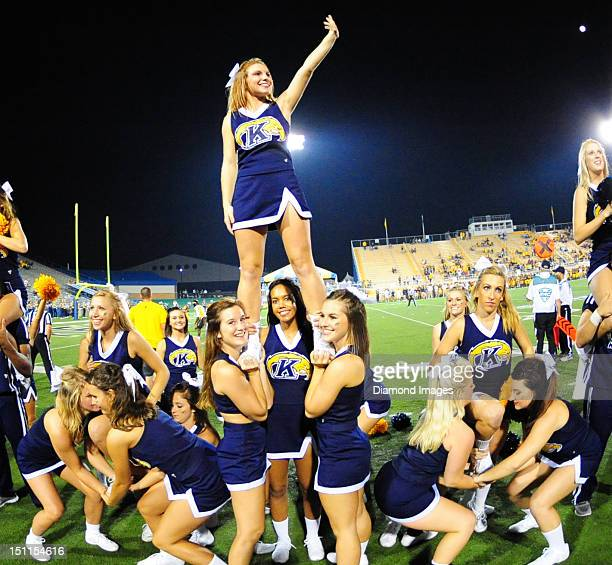 Cheerleaders for the Kent State Golden Flashes perform a cheer on the sideline during a game between the Kent State Golden Flashes and the Towson...