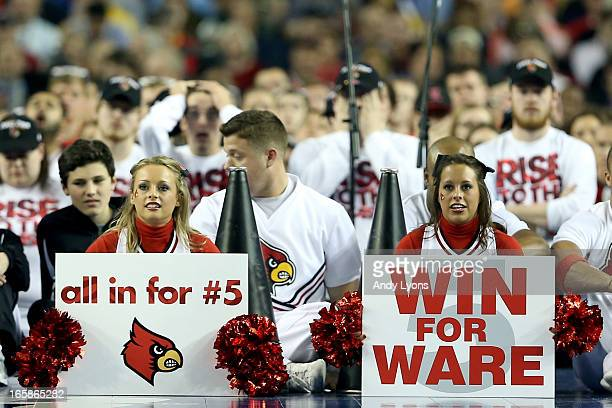 Cheerleaders for the Louisville Cardinals hold up signs in support of injured guard Kevin Ware in the second half against the Wichita State Shockers...