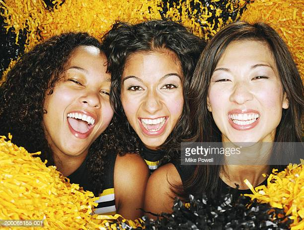 Cheerleaders holding pompoms, laughing, portrait, close-up