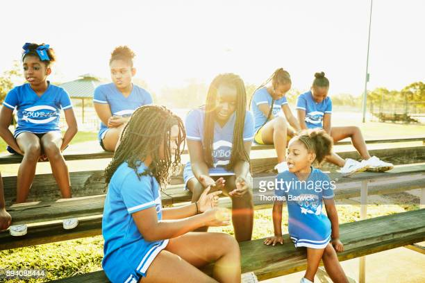 Cheerleaders in discussion with young teammate while sitting on bleachers in park before morning practice
