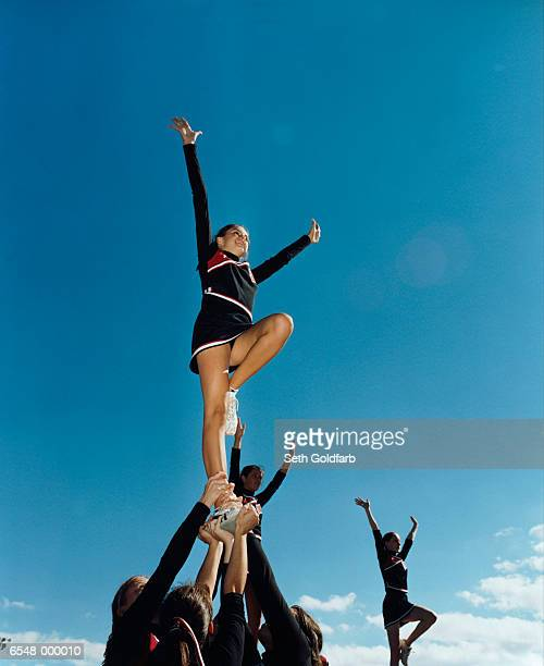 cheerleaders in formation - cheerleaders stock photos and pictures