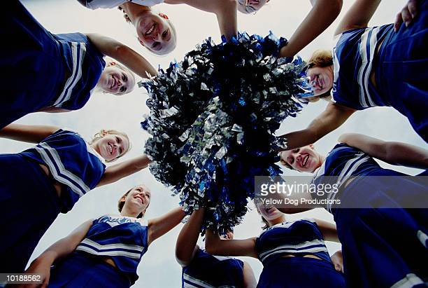 Cheerleaders in huddle with pom-poms