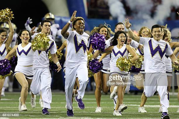 Cheerleaders lead the Washington Huskies onto the field for the College Football Playoff Semifinal at the ChickfilA Peach Bowl between the Washington...