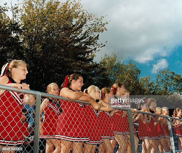 cheerleaders leaning on fence - cheerleader up skirt stock photos and pictures