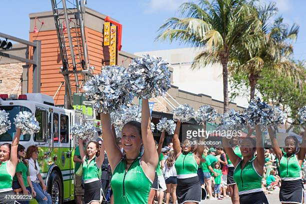 cheerleaders march in st. patrick's day parade - delray beach stock photos and pictures