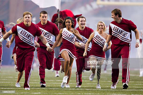Cheerleaders of the Arkansas Razorbacks lead the team onto the field before a game against the Kentucky Wildcats at Razorback Stadium on October 13...