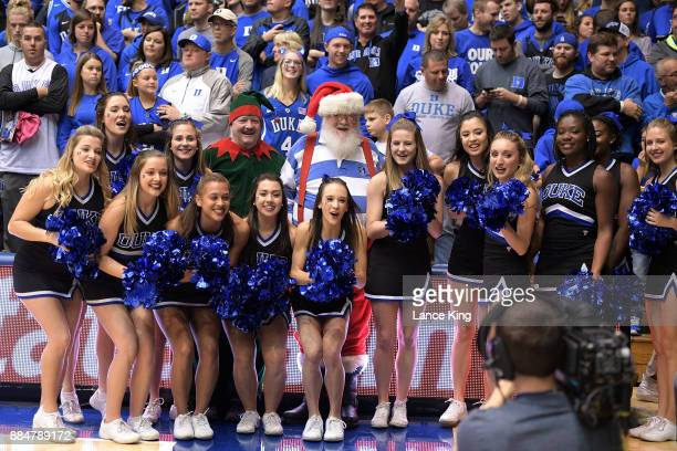 Cheerleaders of the Duke Blue Devils pose with fans dressed as an Elf and Santa Claus prior to their game against the South Dakota Coyotes at Cameron...