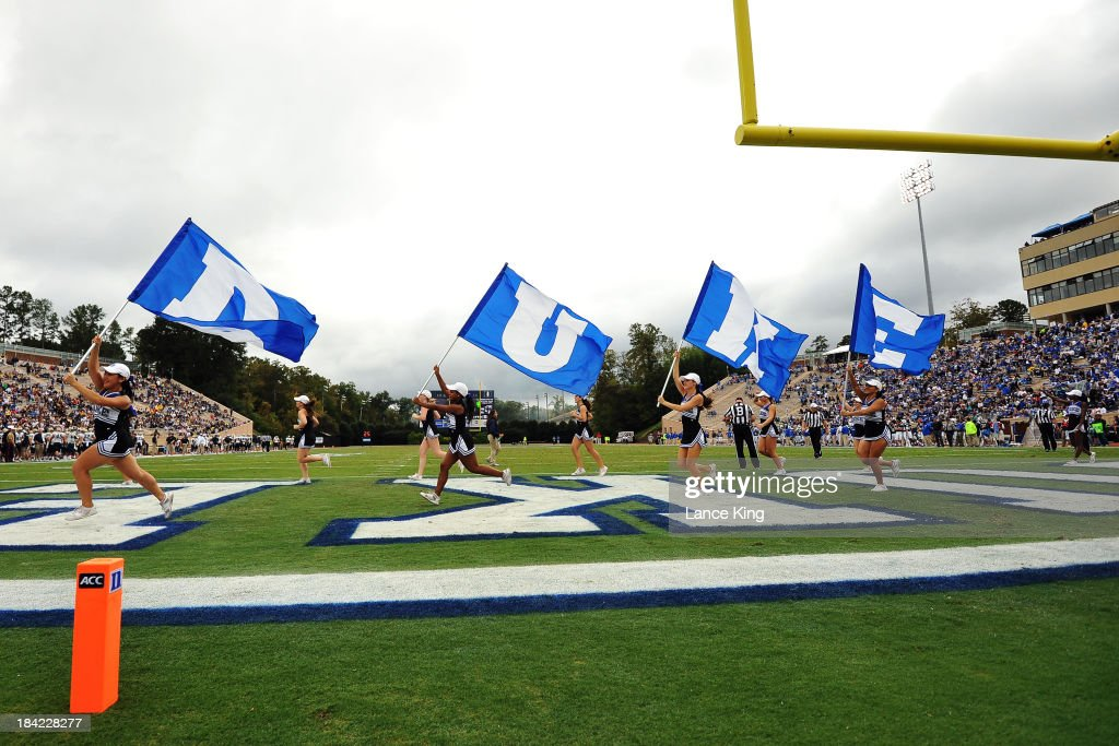 Cheerleaders of the Duke Blue Devils run on the field with flags following a Duke touchdown against the Navy Midshipmen at Wallace Wade Stadium on October 12, 2013 in Durham, North Carolina. Duke defeated Navy 35-7.