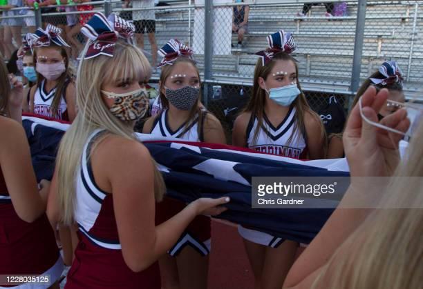 Cheerleaders of the Herriman Mustangs carry the American Flag at Mustang Stadium on August 13, 2020 in Herriman, Utah. The Mustangs faced the Davis...