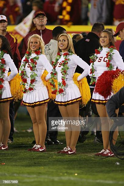 Cheerleaders of the USC Trojans smile with roses around their necks while watching the videoboard from the sideline during the game against the UCLA...