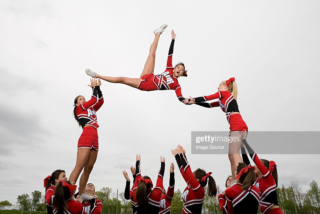 Cheerleaders performing routine : Stock Photo